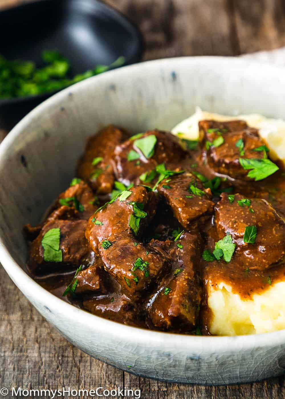 Beef Tips and mashed potatoes garnished with chopped parsley