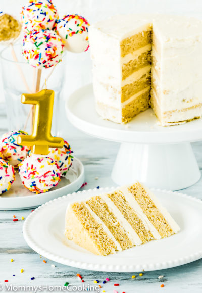 eggless smash cake sliced with cake pops and a candle on the background