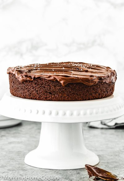 One Bowl Eggless Chocolate Cake on a cake stand with ganache frosting