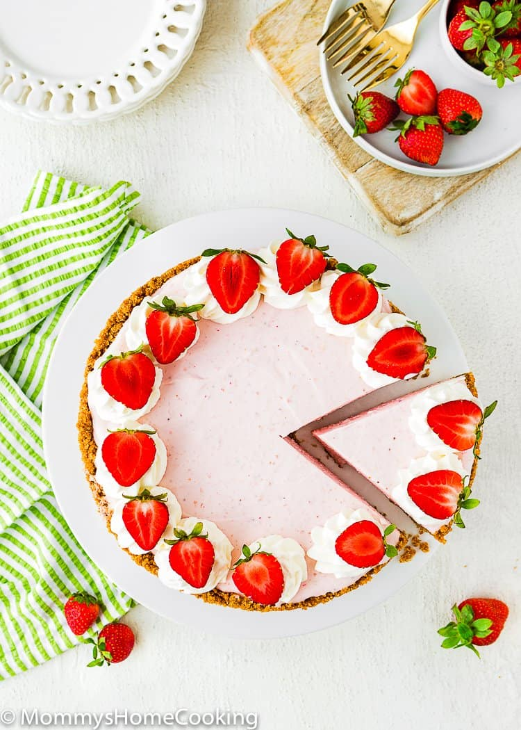 sliced No-Bake Strawberry Cheesecake with whipped cream and fresh strawberries