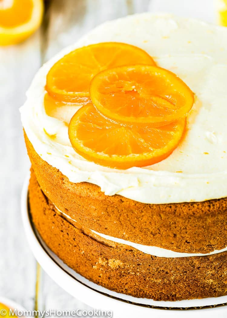 Easy Eggless Orange Cake decorate it with candied orange sliced and orange buttercream