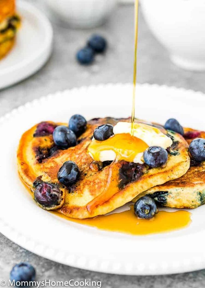 Easy Eggless Blueberry Pancakes in a plate with syrup and butter