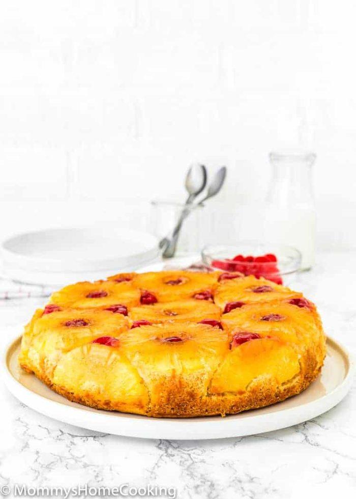 a whole Eggless Pineapple Upside Down Cake over a cake plate