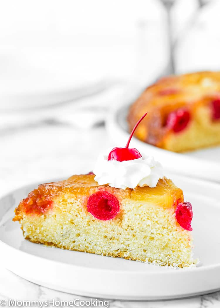 slice of Eggless Pineapple Upside Down Cake with whipped cream and a cherry