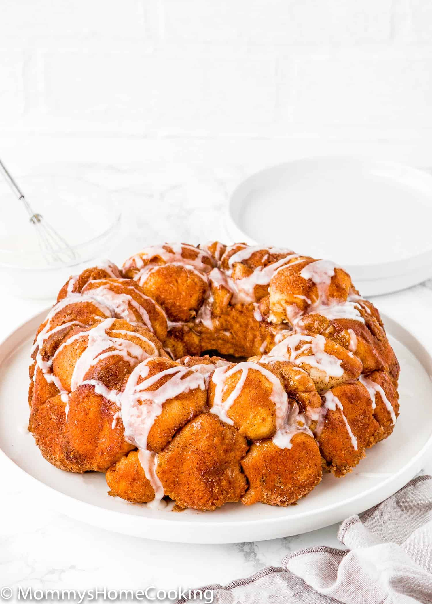 Homemade Eggless Monkey Bread on a plate drizzled with sugar glaze