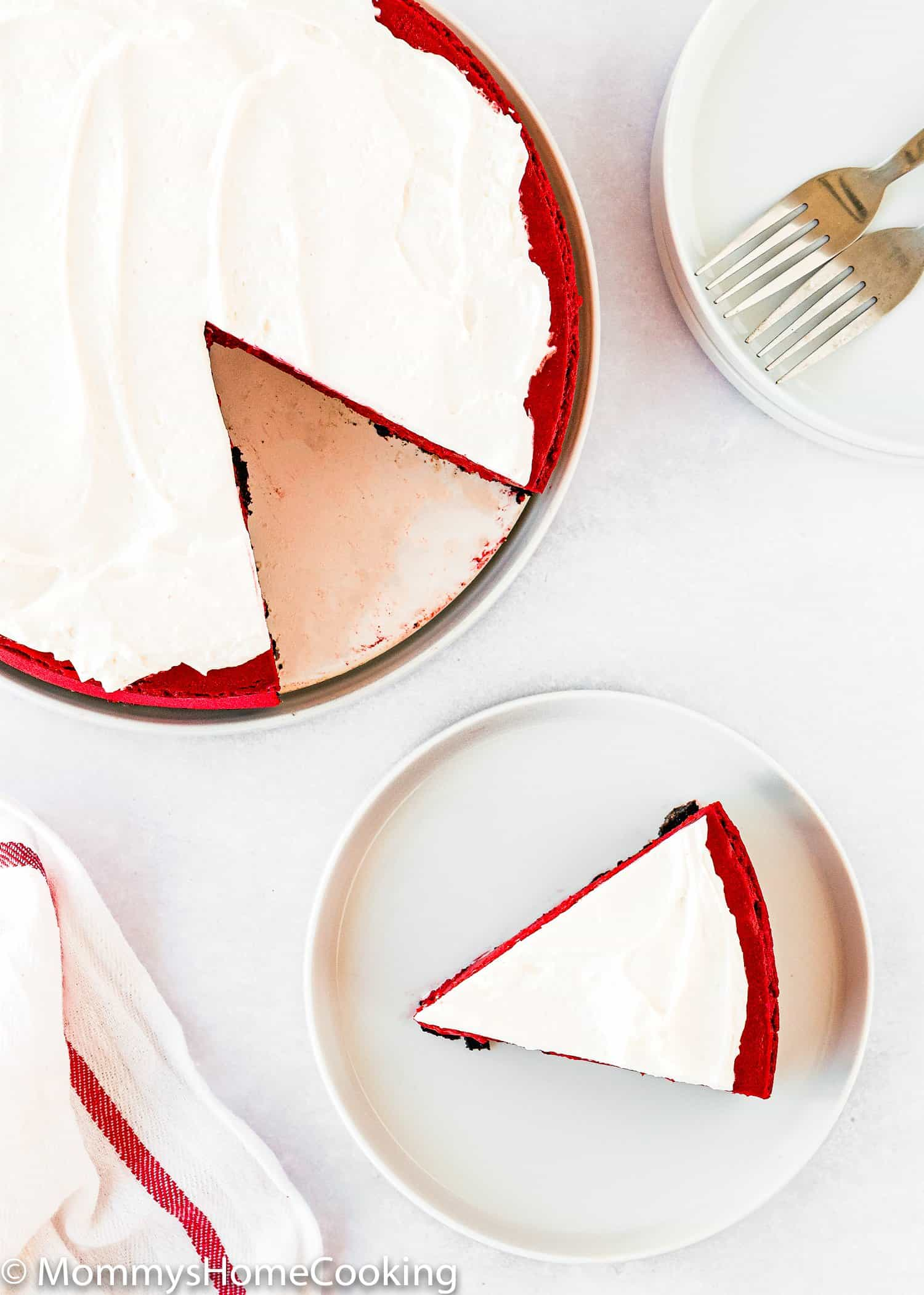 cut Eggless Red Velvet Cheesecake over a white surface