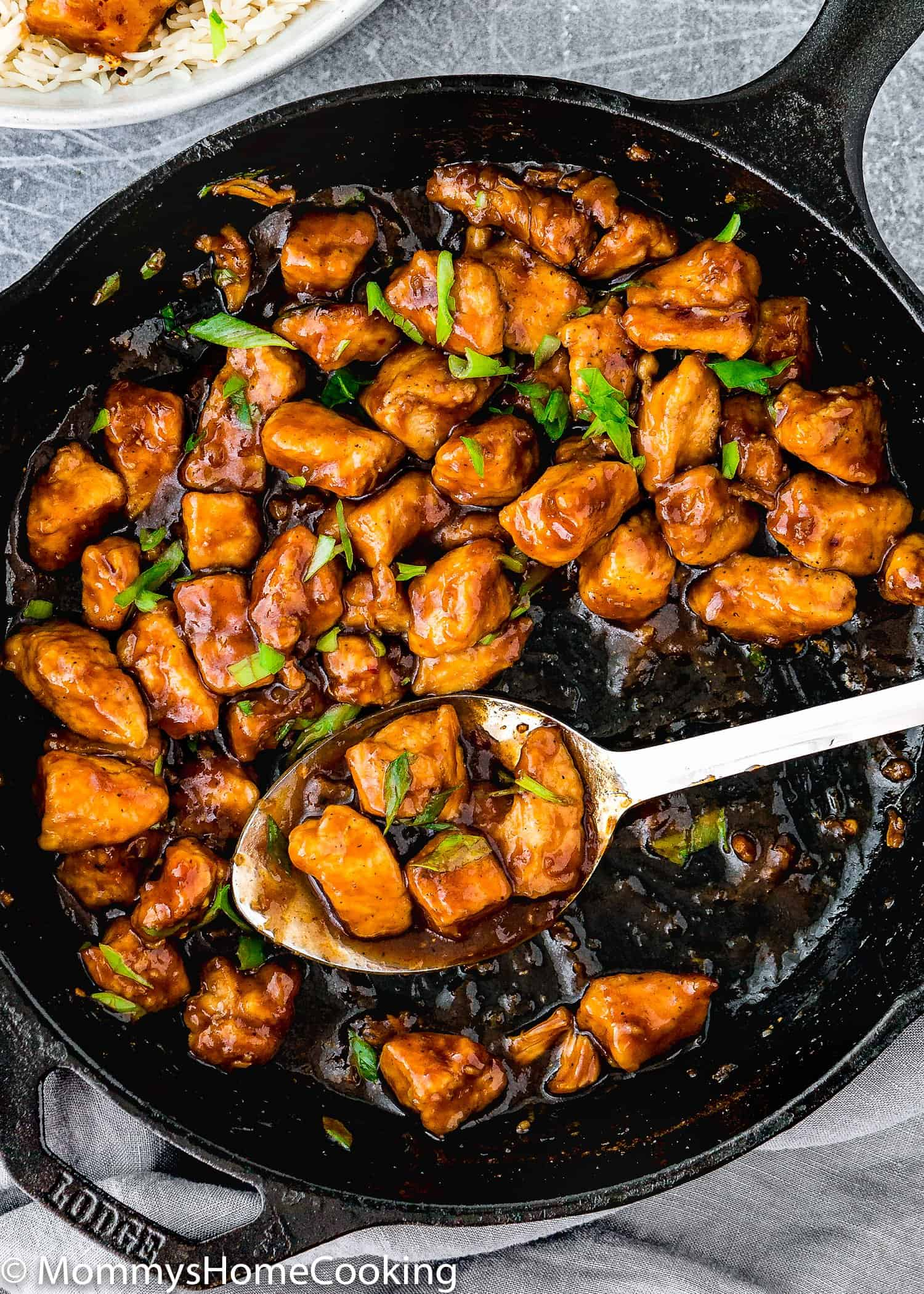 Easy Sticky Bourbon Chicken in a skillet with a serving spoon