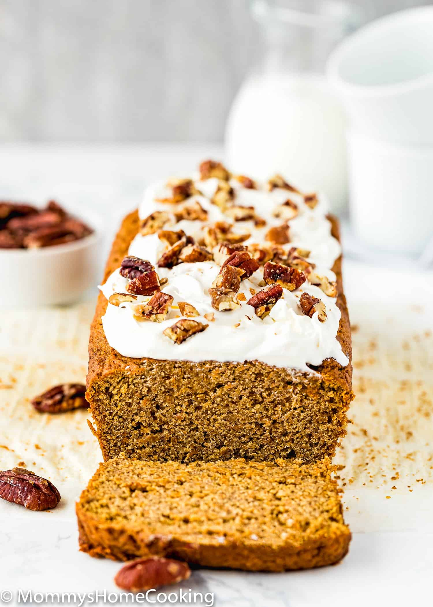 sliced Eggless Carrot Cake quick bread with frosting and chopped pecans
