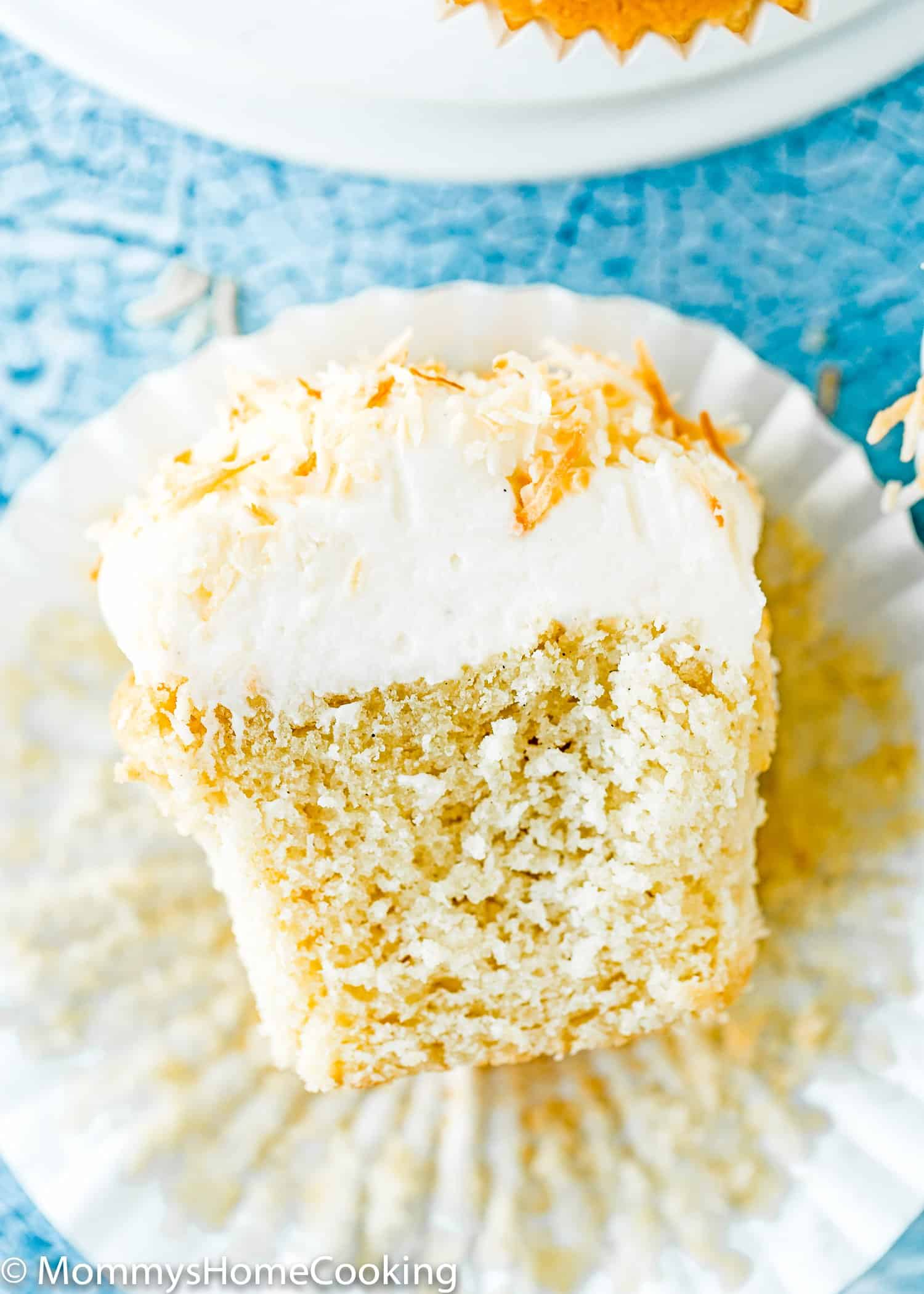 Eggless Coconut Cupcake cut open showing the fluffy inside texture