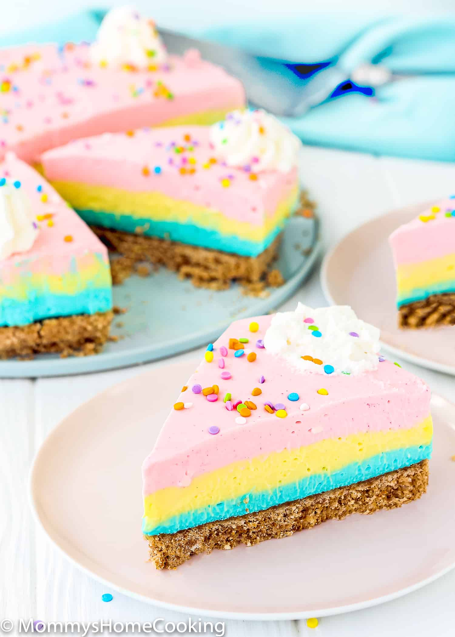 a slice of a pink, yellow and blue no-bake cheesecake over a pink plate