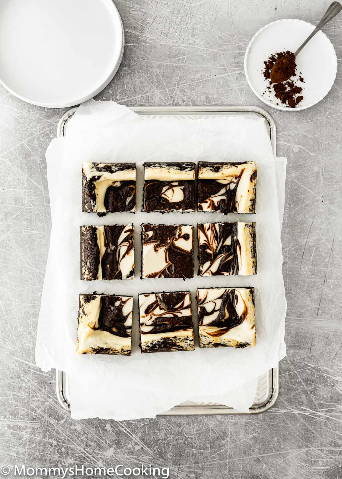 Eggless Cheesecake Brownies squares over a baking tray with parchment paper