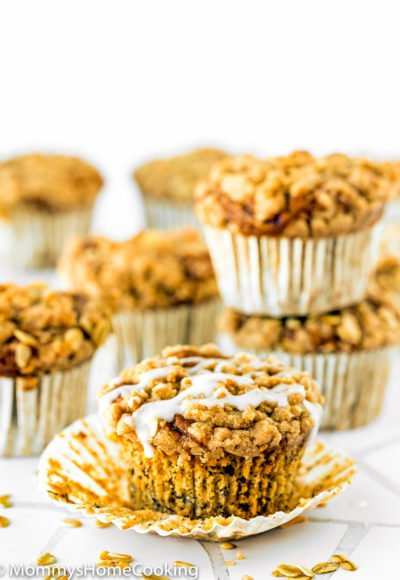 eggless banana crumb muffins with glaze over a white surface