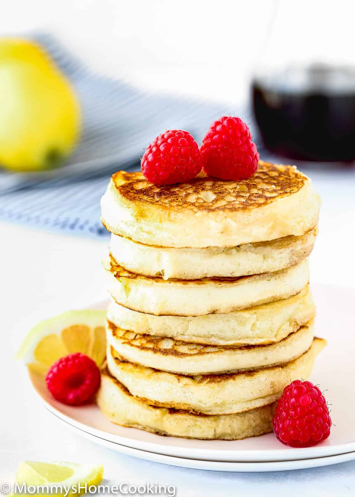 stack of eggless lemon Ricotta pancakes with Raspberries and a lemon slice on a plate.