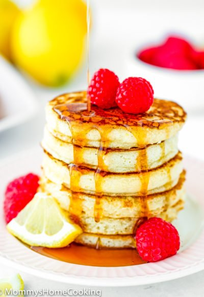 maple syrup poured over a stack of eggless lemon Ricotta pancakes