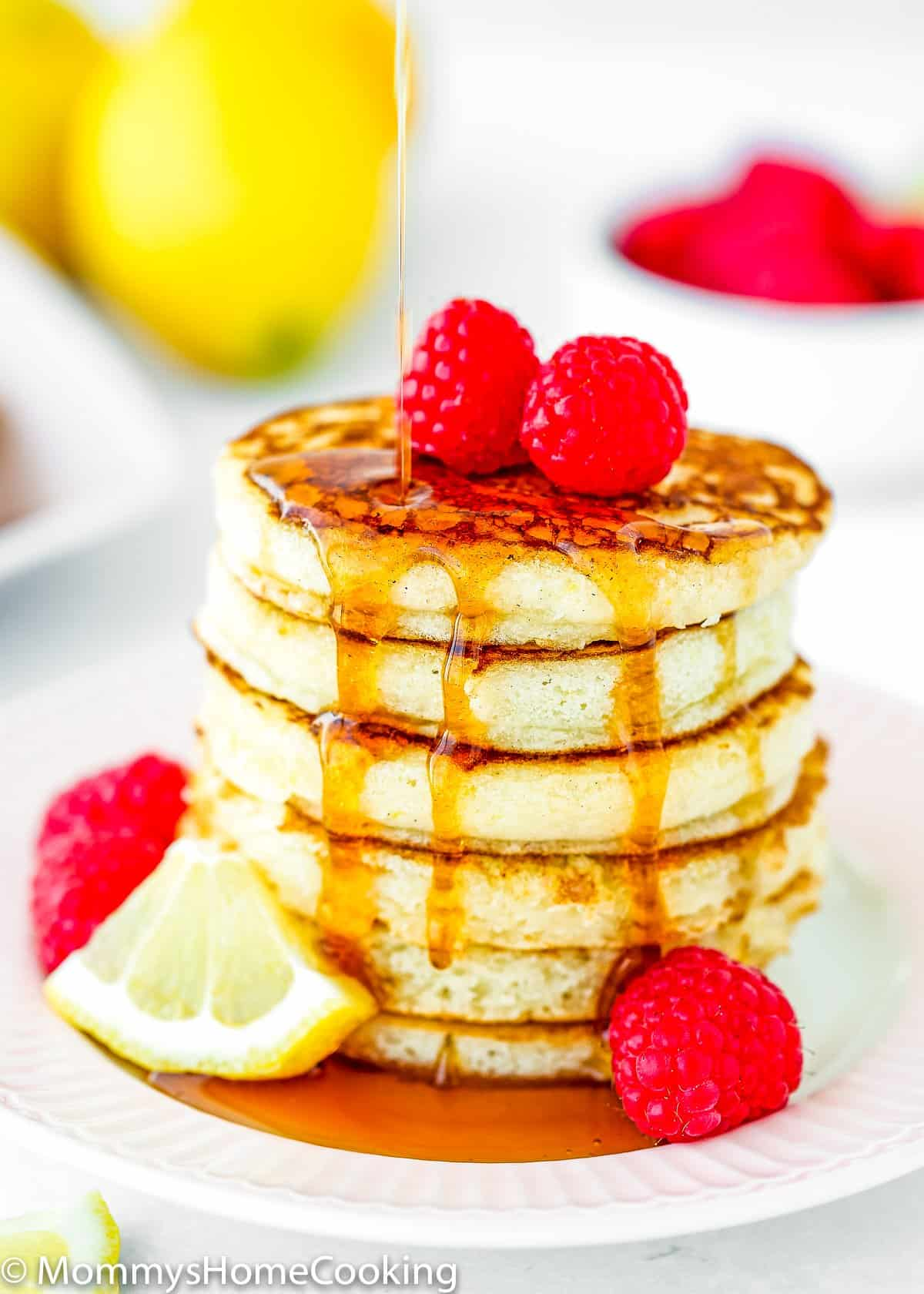 maple syrup poured onto a stack of eggless lemon ricotta pancakes.