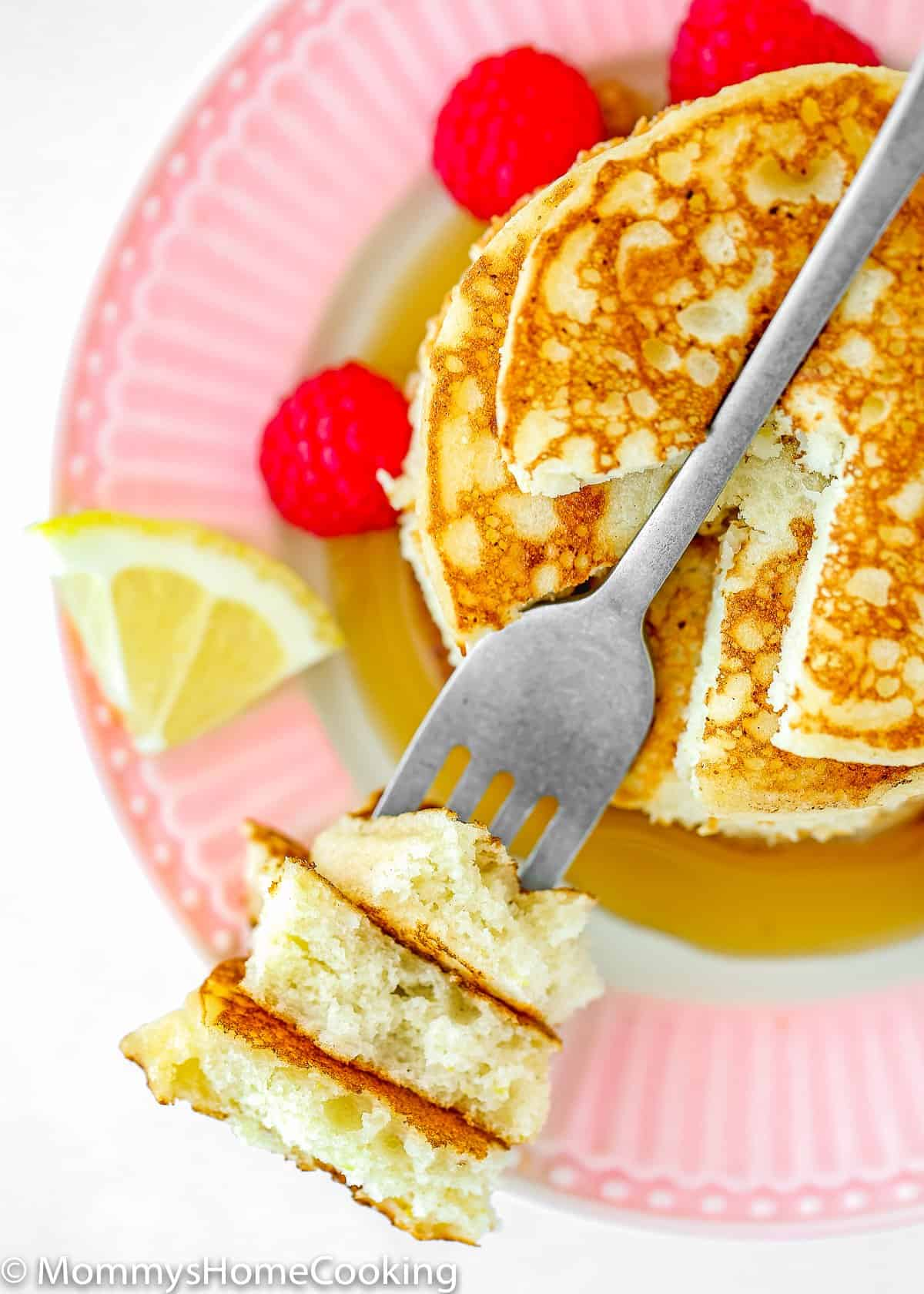 a fork with eggless lemon pancakes showing fluffy inside texture.