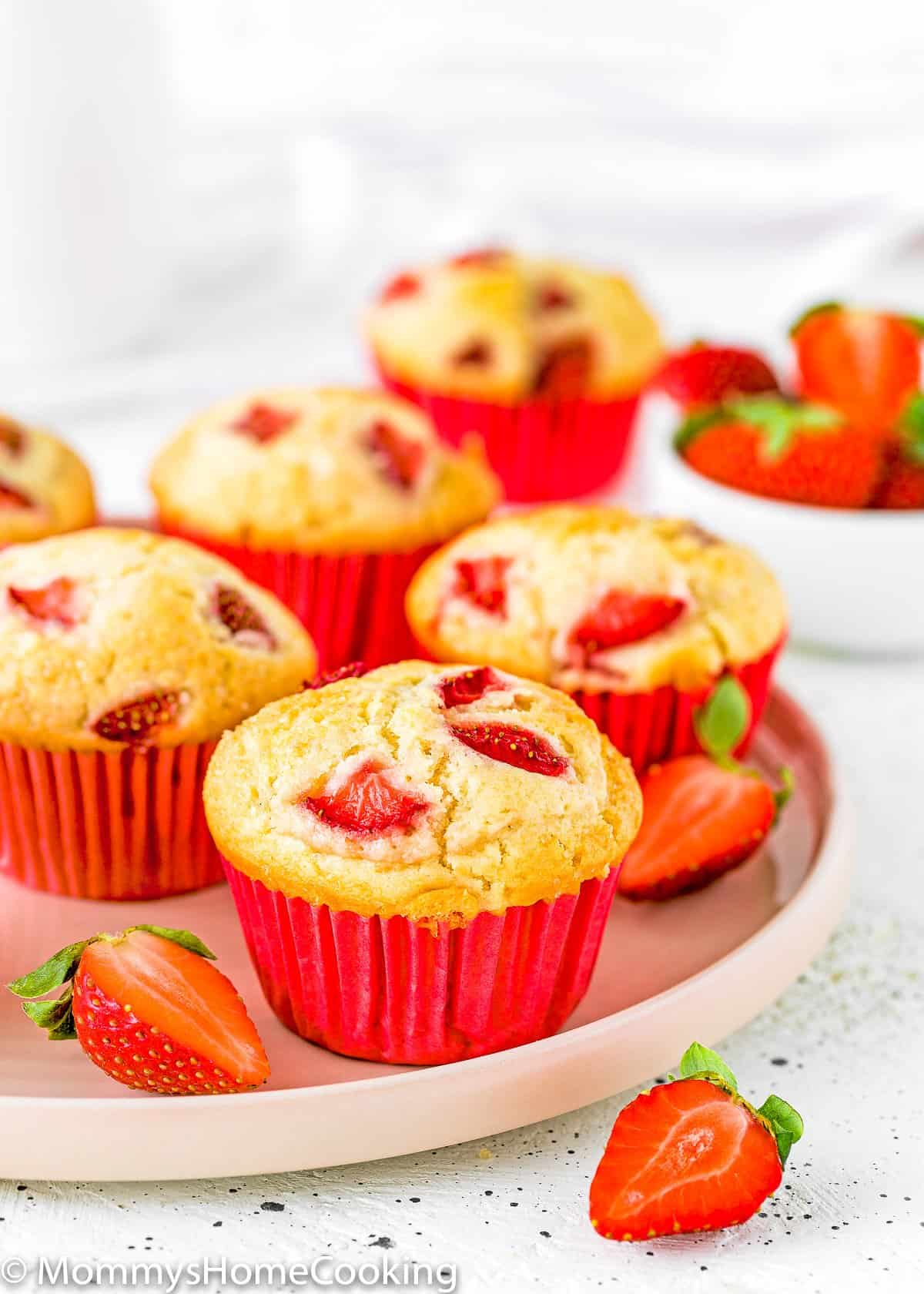 eggless strawberry muffins with fresh sliced strawberries on a plate