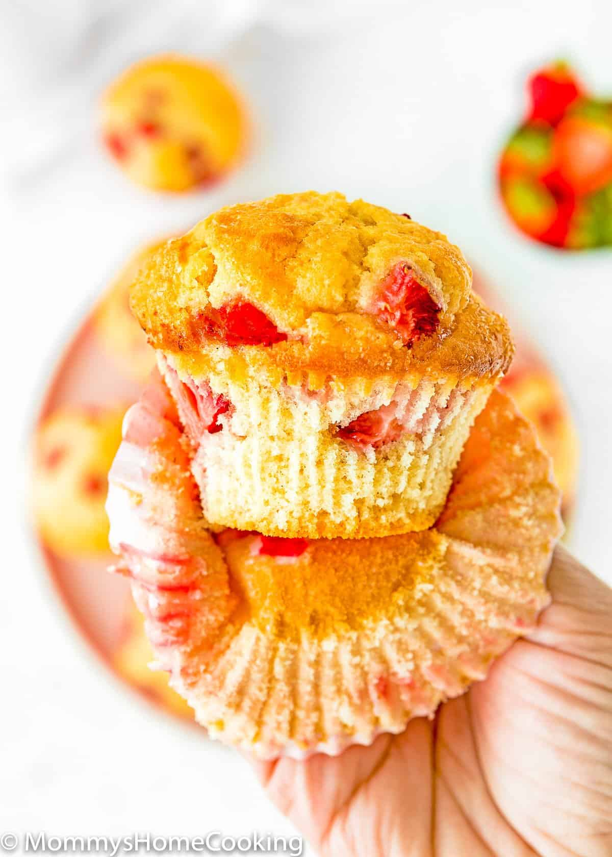 a hand holding a perfect eggless strawberry muffin
