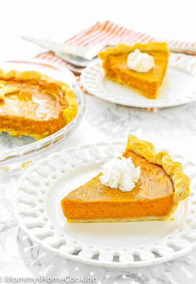 two Eggless Pumpkin Pie slices on white plates over a marble surface