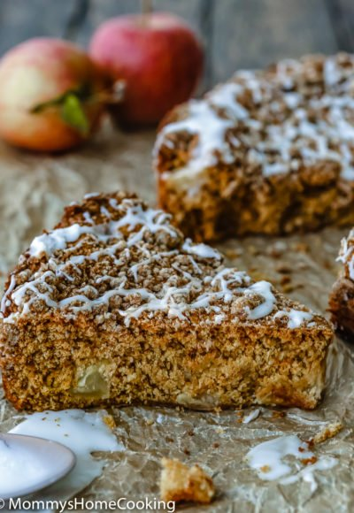 Eggless Apple Maple Spice Cake slice over a parchment paper with red apples in the background