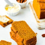 slices of Eggless Pumpkin Bread with butter in the background